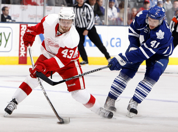 TORONTO - OCTOBER 2: Nikolai Kulemin #41 of the Toronto Maple Leafs slashes Darren Helm #43 of the Detroit Red Wings during a preseason NHL game at the Air Canada Centre October 2, 2010 in Toronto, Ontario, Canada. (Photo by Abelimages/Getty Images)