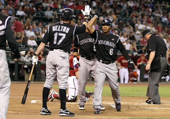 PHOENIX - SEPTEMBER 22:  Melvin Mora #6 of the Colorado Rockies celebrates with Todd Helton #17 after Mora hit a 3 run home run against the Arizona Diamondbacks during the first inning of the Major League Baseball game at Chase Field on September 22, 2010