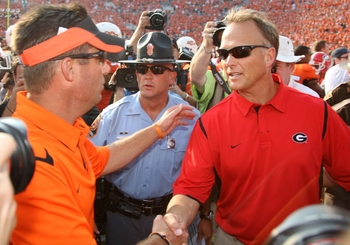 STILLWATER, OK - SEPTEMBER 5:  Head coach Mark Richt of the Georgia Bulldogs congratulates head coach Mike Gundy of the Oklahoma State Cowboys after the Cowboys won the game 24-10 at Boone Pickens Stadium on September 5, 2009 in Stillwater, Oklahoma. (Pho