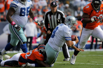 DENVER - OCTOBER 04:  Elivs Dumervil #92 of the Denver Broncos sacks quarterback Tony Romo #9 of the Dallas Cowboys during NFL action at Invesco Field at Mile High on October 4, 2009 in Denver, Colorado. The Broncos defeated the Cowboys 17-10.  (Photo by