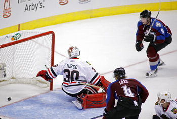 DENVER, CO - OCTOBER 7: John-Michael Liles #4 and Matt Duchene #9 of the Colorado Avalanche close in on Marty Turco #30 of the Chicago Blackhawks as a shot by Paul Stastny (not pictured) trickles past Turco in overtime during both team's season openers at