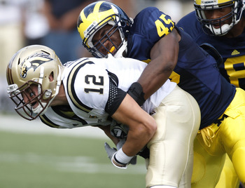 ANN ARBOR, MI - SEPTEMBER 5:  Obi Ezeh #45 of the Michigan Wolverines tackles Robert Arnheim #12 of the Western Michigan Broncos during the game on September 5, 2009 at Michigan Stadium in Ann Arbor, Michigan. (Photo by Gregory Shamus/Getty Images)