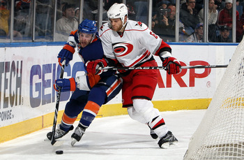 UNIONDALE, NY - FEBRUARY 06:  Tim Gleason #6 of the Carolina Hurricanes checks Andrew MacDonald #47 of the New York Islanders on February 6, 2010 at Nassau Coliseum in Uniondale, New York.  (Photo by Jim McIsaac/Getty Images)