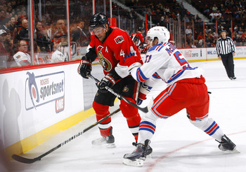KANATA, ON - OCTOBER 02:  Chris Phillips #4 of the Ottawa Senators and Ryan McDonagh #51 of the New York Rangers battle for the puck along the near boards at Scotiabank Place on October 2, 2010 in Kanata, Ontario, Canada.  The Ottawa Senators defeated the