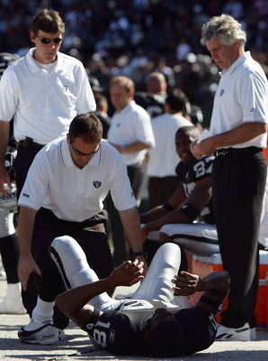 OAKLAND, CA - OCTOBER 16:  Wide receiver Randy Moss #18 of the Oakland Raiders is attended to on the sideline after sustaining an injury during the first quarter of the game against the San Diego Chargers at McAfee Coliseum on October 16, 2005 in Oakland,