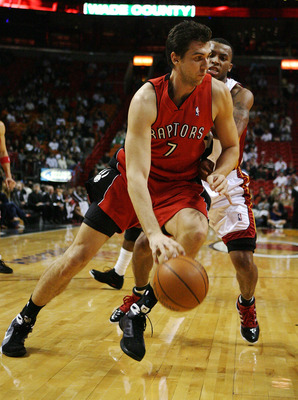 MIAMI - NOVEMBER 19:  Andrea Bargnani #7 of the Toronto Raptors drives past Daequan Cook #14 of the Miami Heat at American Airlines Arena on November 19, 2008 in Miami, Florida. The Raptors defeated the Heat 101-95. NOTE TO USER: User expressly acknowledg
