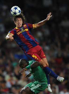 BARCELONA, SPAIN - SEPTEMBER 14:  Carles Puyol of Barcelona duels for a high ball with Djibril Cisse of Panathinaikos during the UEFA Champions League group D match between Barcelona and Panathinaikos on September 14, 2010 in Barcelona, Spain. Barcelona w