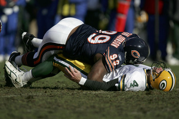 CHICAGO - DECEMBER 4:  Tank Johnson #99 of the Chicago Bears drops Brett Favre #4 of the Green Bay Packers and gets penalized for roughing the passer during their game on December 4, 2005 at Soldier Field in Chicago, Illinois.  (Photo by Jonathan Daniel/G