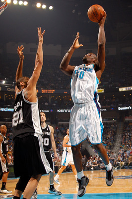 NEW ORLEANS - JANUARY 18:  Emeka Okafor #50 of the New Orleans Hornets shoots the ball over Tim Duncan #21 of the San Antonio Spurs at New Orleans Arena on January 18, 2010 in New Orleans, Louisiana.   NOTE TO USER: User expressly acknowledges and agrees