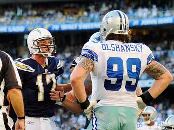 SAN DIEGO - AUGUST 21:  Quarterback Philip Rivers #17 of the San Diego Chargers reacts to Igor Olshansky #99 of the Dallas Cowboys after scoring a touchdown on a one yard rush to the end zone during their pre-season NFL football game at Qualcomm Stadium o