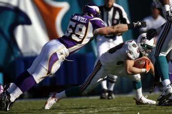 MIAMI - NOVEMBER 19:  Wide receiver Wes Welker #83 of the Miami Dolphins tries to evade Linebacker Heath Farwell #59 of the Minnesota Vikings in the fourth quarter at Miami Dolphin Stadium November 19, 2006 in Miami, Florida.  (Photo by Eliot J. Schechter