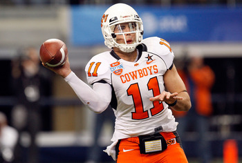 ARLINGTON, TX - JANUARY 02:  Quarterback Zac Robinson #11 of the Oklahoma State Cowboys drops back to pass against the Mississippi Rebels during the AT&T Cotton Bowl on January 2, 2010 at Cowboys Stadium in Arlington, Texas.  (Photo by Ronald Martinez/Get