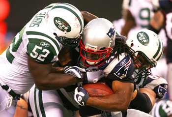 EAST RUTHERFORD, NJ - SEPTEMBER 19: BenJarvus Green-Ellis #42 of the New England Patriots is tackled by David Harris #52 of the New York Jets at the New Meadowlands Stadium on September 19, 2010 in East Rutherford, New Jersey. The Jets defeated the Patrio