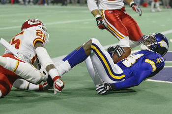 MINNEAPOLIS - DECEMBER 20:  Randy Moss #84 of the Minnesota Vikings falls into the endzone for a touchdown as Greg Wesley #25 of the Kansas City Chiefs defends on December 20, 2003 at the Hubert H. Humphrey Metrodome in Minneapolis, Minnesota.  (Photo by