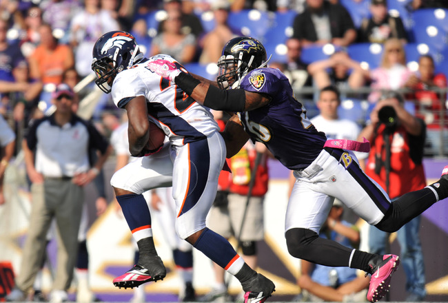BALTIMORE, MD - OCTOBER 10:  Correll Buckhalter #28 of the Denver Broncos runs the ball against the Baltimore Ravens while Dawan Landry #26 defends at M&T Bank Stadium on October 10, 2010 in Baltimore, Maryland. Players wore pink in recognition of Breast