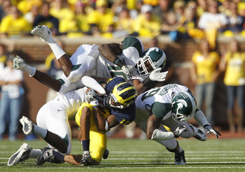 ANN ARBOR, MI - OCTOBER 09: Chris Norman #10 and Trenton Robinson #39 of the Michigan State Spartans make the stop on Dana Dixon #12 of the Michigan Wolverines during the game on October 9, 2010 at Michigan Stadium in Ann Arbor, Michigan. (Photo by Leon H