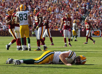 LANDOVER, MD - OCTOBER 10:  Aaron Rodgers #12 of the Green Bay Packers lays on the ground after a hard hit against the Washington Redskins in the fourth quarter at FedExField on October 10, 2010 in Landover, Maryland. The Redskins won the game in overtime