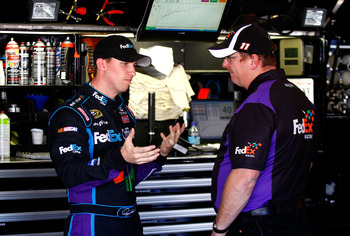 FONTANA, CA - OCTOBER 08:  (L-R) Denny Hamlin, driver of the #11 FedEx Office Toyota, speaks with crew chief Michael Ford during practice for the NASCAR Sprint Cup Series Pepsi Max 400 on October 8, 2010 in Fontana, California.  (Photo by Jason Smith/Gett