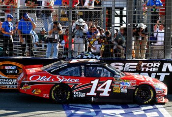 FONTANA, CA - OCTOBER 10:  Tony Stewart, driver of the #14 Office Depot Chevrolet, is handed the checkered flag after winning the NASCAR Sprint Cup Series Pepsi Max 400 on October 10, 2010 in Fontana, California.  (Photo by Jason Smith/Getty Images for NA