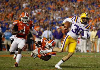 GAINESVILLE, FL - OCTOBER 09:  Punter Josh Jasper #30 of the Louisiana State Tigers runs a fake punt for yardage past Ahmad Black #35 and Janoris Jenkins #1 of the Florida Gators during the game at Ben Hill Griffin Stadium on October 9, 2010 in Gainesvill