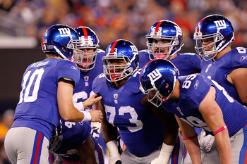 EAST RUTHERFORD, NJ - OCTOBER 03:  Eli Manning #10 of the New York Giants talks to David Diehl #66, Shawn Andrews #73, Rich Seubert #69, Adam Koets #61 and Kevin Boss #89 in the huddle against the Chicago Bears at New Meadowlands Stadium on October 3, 201