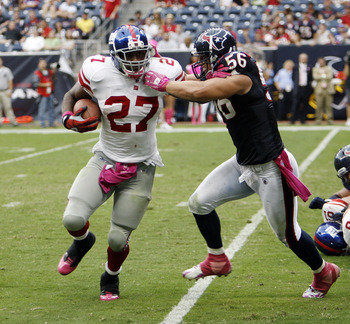 HOUSTON - OCTOBER 10:  Running back Brandon Jacobs #27 of the New York Giants eludes the tackle of linebacker  Brian Cushing #56 of the Houston Texans at Reliant Stadium on October 10, 2010 in Houston, Texas. New York won 34-10.  (Photo by Bob Levey/Getty