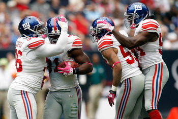 HOUSTON - OCTOBER 10:  Justin Tuck #91 of the New York Giants celebrates after recovering a fumble during the game against the Houston Texans at Reliant Stadium on October 10, 2010 in Houston, Texas.  The Giants defeated the Texans 34-10.  (Photo by Chris