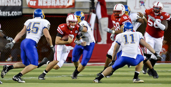 LINCOLN, NEBRASKA - SEPTEMBER 25: Nebraska Cornhuskers quarterback Taylor Martinez #3, with the help of teammates offensive linesmen Keith Williams #68 and Mike Caputo #58 works his way through the South Dakota State Jackrabbit defense during their game a