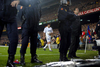 BARCELONA - NOVEMBER 23:  Luis Figo of Real Madrid prepares to take a corner with a police escort during the La Liga match between FC Barcelona and Real Madrid played at the Nou Camp Stadium, Barcelona, Spain on November 23, 2002. (Photo by Firo Foto/Gett