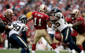 SAN FRANCISCO, CA - OCTOBER 15:  Quarterback Alex Smith #11 of the San Francisco 49ers fumbles the ball after being hit by Shaun Phillips #95 of the San Diego Chargers at Monster Park October 15, 2006 in San Francisco, California.  (Photo by Jonathan Ferr