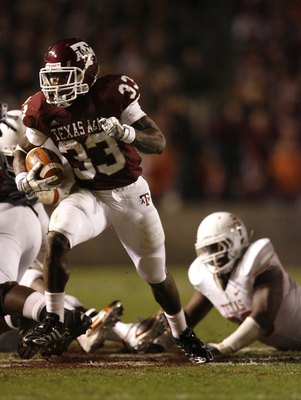 COLLEGE STATION, TX - NOVEMBER 26: Tailback Christine Michael #33 of the Texas A&M Aggies rushes for a gain against the Texas Longhorns defense in the second half at Kyle Field on November 26, 2009 in College Station, Texas. The Longhorns defeated the Agg