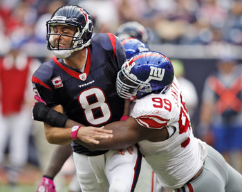 HOUSTON - OCTOBER 10:  Quarterback Matt Schaub #8 of the Houston Texans is hit by defensive tackle Chris Canty #99 of the New York Giants at Reliant Stadium on October 10, 2010 in Houston, Texas.  (Photo by Bob Levey/Getty Images)