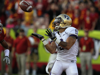 LOS ANGELES, CA - OCTOBER 02:  Wide Receiver Devin Aguilar #9 of the Washington Huskies catches a 44 yard touchdown pass in the end zone against cornerback Torin Harris #4 of the USC Trojans in the second quarter at the Los Angeles Memorial Coliseum on Oc