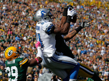 GREEN BAY, WI - OCTOBER 03: Calvin Johnson #81 of the Detroit Lions leaps to catch a touchdown pass between Derrick Martin #29 and Charles Woodson #21 of the Green Bay Packers at Lambeau Field on October 3, 2010 in Green Bay, Wisconsin. (Photo by Jonathan