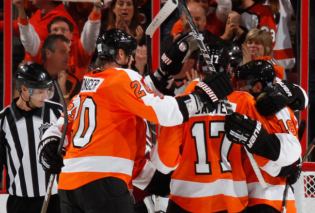 PHILADELPHIA - OCTOBER 11:  Teammates mob Jeff Carter #17 of the Philadelphia Flyers after he scored the Flyers winning goal in the third period of a hockey game against the Colorado Avalanche at the Wells Fargo Center on October 11, 2010 in Philadelphia,