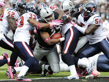 OAKLAND, CA - OCTOBER 3: Running back Michael Bush #29 of the Oakland Raiders drags Troy Nolan #33 and DeMeco Ryans #59 of the Houston Texans into the endzone for a touchdown during an NFL football game October 3, 2010 at The Oakland-Alameda County Colise