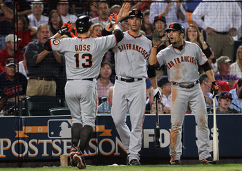 ATLANTA - OCTOBER 11:  Cody Ross #13 of the San Francisco Giants is congratulated by Madison Bumgerner #40 and Andres Torres #56 after hitting a home run during the 6th inning of Game Four of the NLDS of the 2010 MLB Playoffs against the Atlanta Braves on