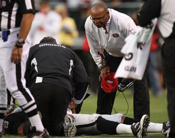 OAKLAND, CA - AUGUST 28: Jason Campbell #8 of the Oakland Raiders lies on the ground injured as head coach Mike Singletary of the San Francisco 49ers looks on during an NFL preseason game at Oakland-Alameda County Coliseum on August 28, 2010 in Oakland, C