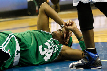 ORLANDO, FL - MAY 18:  Paul Pierce #34 of the Boston Celtics lies on the court in pain after he drew contact from Dwight Howard #12 of the Orlando Magic in the second quarter of Game Two of the Eastern Conference Finals during the 2010 NBA Playoffs at Amw