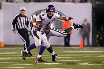 EAST RUTHERFORD, NJ - OCTOBER 11:  Quarterback Brett Favre #4 of the Minnesota Vikings attempts to escape the pressure from Shaun Ellis #92 of the New York Jets at New Meadowlands Stadium on October 11, 2010 in East Rutherford, New Jersey.  (Photo by Jim