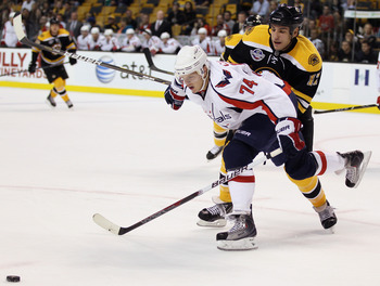 BOSTON - SEPTEMBER 29:  Milan Lucic #17 of the Boston Bruins and John Carlson #74 of the Washington Capitals fight for the puck on September 29, 2010 at the TD Garden in Boston, Massachusetts. The Capitals defeated the Bruins 4-1.  (Photo by Elsa/Getty Im