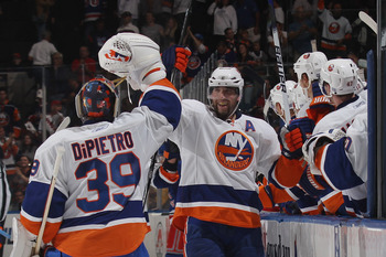UNIONDALE, NY - OCTOBER 11: Trent Hunter #7  of the New York Islanders high fives Rick DiPietro #39 following the Islanders go ahead goal in the third period against the New York Rangers at the Nassau Coliseum on October 11, 2010 in Uniondale, New York. (