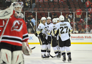 NEWARK, NJ - OCTOBER 11: Martin Brodeur #30 of the New Jersey Devils (Center-L) skates back to his position as Paul Martin #7 of the Pittsburgh Penguins (third from left) is congratulated after scoring an empty net goal in the third period at the Prudenti