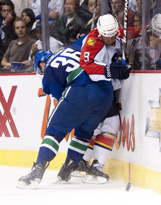 VANCOUVER, CANADA - OCTOBER 11: Jannik Hansen #36 of the Vancouver Canucks hits Stephen Weiss #9 of the Florida Panthers into the end boards during the third period in NHL action on October 11, 2010 at Rogers Arena in Vancouver, British Columbia, Canada.