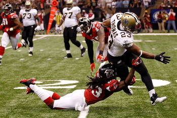 NEW ORLEANS - SEPTEMBER 26:  Pierre Thomas #23 of the New Orleans Saints is tackled for a loss by Dunta Robinson #23 of the Atlanta Falcons at the Louisiana Superdome on September 26, 2010 in New Orleans, Louisiana.  (Photo by Chris Graythen/Getty Images)