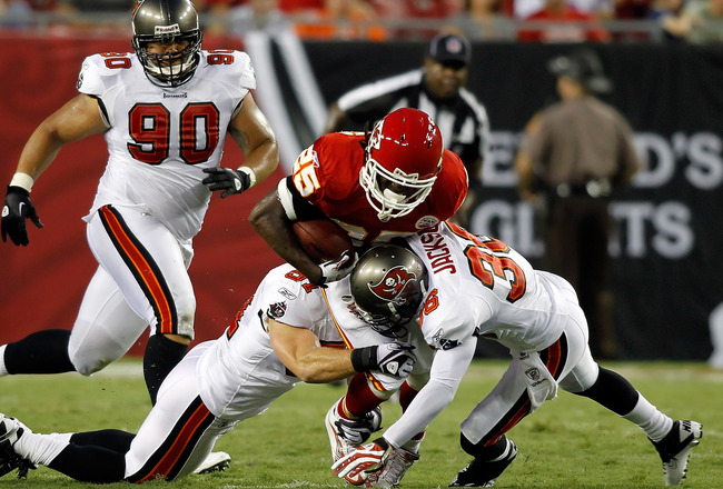 TAMPA, FL - AUGUST 21:  Defenders Barrett Ruud #51 and Tanard Jackson #36 of the Tampa Bay Buccaneers tackle running back Jamaal Charles #25 of the Kansas City Chiefs during a preseason game at Raymond James Stadium on August 21, 2010 in Tampa, Florida.