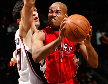 ATLANTA - DECEMBER 02:  Jarrett Jack #1 of the Toronto Raptors drives against Zaza Pachulia #27 of the Atlanta Hawks at Philips Arena on December 2, 2009 in Atlanta, Georgia.  NOTE TO USER: User expressly acknowledges and agrees that, by downloading and/o