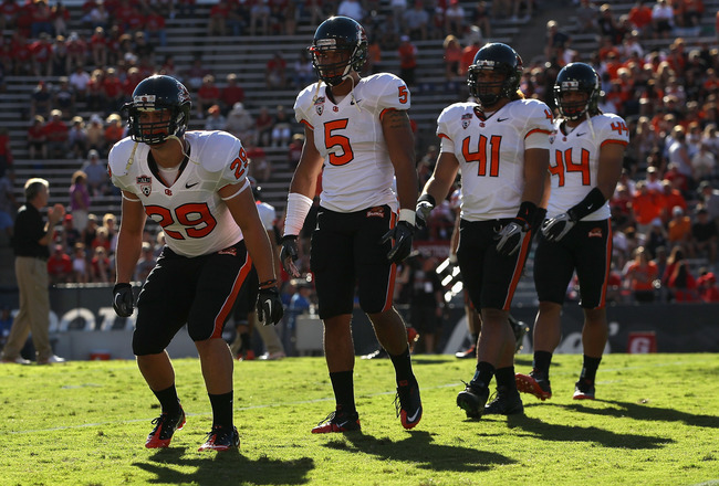 TUCSON, AZ - OCTOBER 09:  (L-R) Zane Norris #29,  Cameron Collins #5, Feti Unga #41 and Uani Unga #44 of the Oregon State Beavers warm up before the college football game against the Arizona Wildcats at Arizona Stadium on October 9, 2010 in Tucson, Arizon