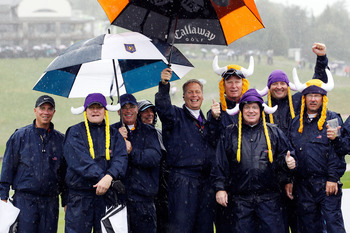 NEWPORT, WALES - OCTOBER 01:  Spectators brave the elements as rain falls and play is suspended during the Morning Fourball Matches during the 2010 Ryder Cup at the Celtic Manor Resort on October 1, 2010 in Newport, Wales.  (Photo by Sam Greenwood/Getty I