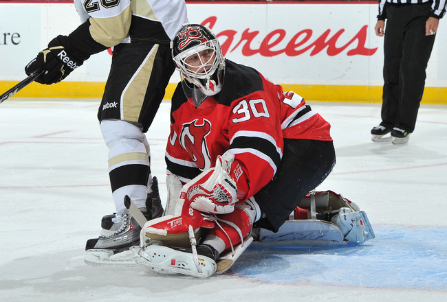 NEWARK, NJ - OCTOBER 11: Eric Tangradi  #26 of the Pittsburgh Penguins and Martin Brodeur #30 of the New Jersey Devils look back at a deflects shot on goal during the first period at the Prudential Center on October 11, 2010 in Newark, New Jersey. The Pen